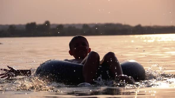 Thumbnail for Silhouette of Happy Boy Swiming on Inflatable Circle in the River at Sunset. Slow Motion