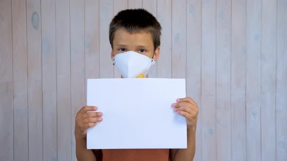 Thumbnail for Little Latin Boy in a Medical Mask Looking at the Camera Holding a Sheet of A4 Paper. Mockup in the