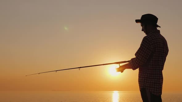 Thumbnail for Silhouette of a Young Fisherman Fishing on the Beach at Sunset