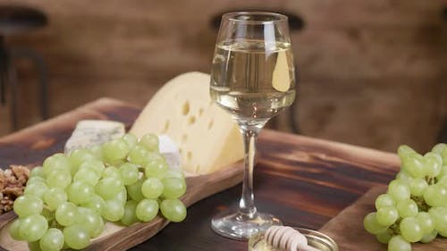 Rotating Composition of Cheese Served with a Glass of Wine and Grapes