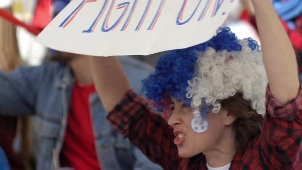 Thumbnail for Female Fan with Banner Cheering at Football Game
