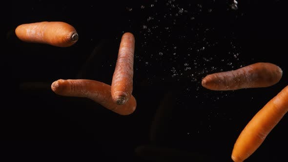 Thumbnail for Carrots Pouring To Water on Black Background. Vegetables Falling Into Water. Slow Motion