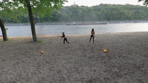 Thumbnail for Two Young Women Performing a Show on the Sand with Flame Standing on the Riverbank