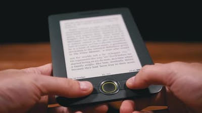 Male Palms Hold a Mobile Electronic Pocket Reader Over a Wooden Table, Reading an E-book