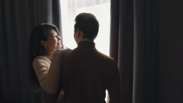 Couple Standing By Window In Hotel