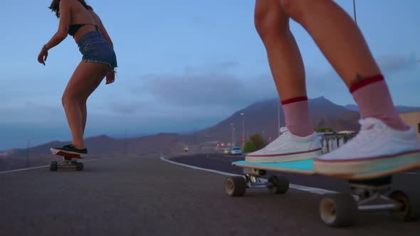 Thumbnail for Close - Up of a Skateboard and Two Girls Who Are Riding on Boards From a Mountain on a Background of
