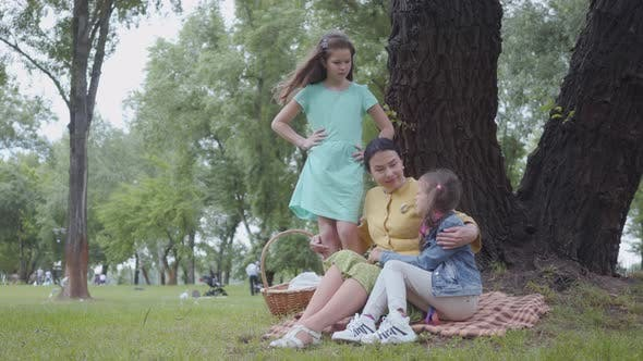 Thumbnail for Mature Happy Grandmother Teaching Her Granddaughters While Sitting in the Beautiful Park