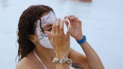 Woman With Mud Face Mask Relaxing In Lagoon