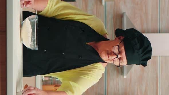 Thumbnail for Vertical Video: Woman Baker Cracking Eggs