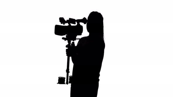 Thumbnail for Videographer Shoots Video in the Studio. White. Silhouette