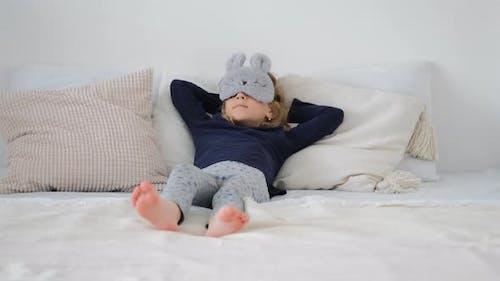 Nettes kleines Mädchen, das zu Hause im Bett liegt