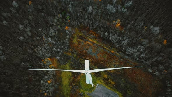 Thumbnail for Drone Moves Backwards, Tilts Up Revealing Windmill Turbine Working in Winter Forest, Renewable