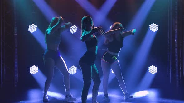 Gruppe von drei verführerischen Tänzern, die in kurzen Shorts ihre Hintern schütteln