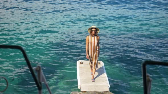 Thumbnail for A woman traveling alone on a dock over the Mediterranean Sea in Italy, Europe