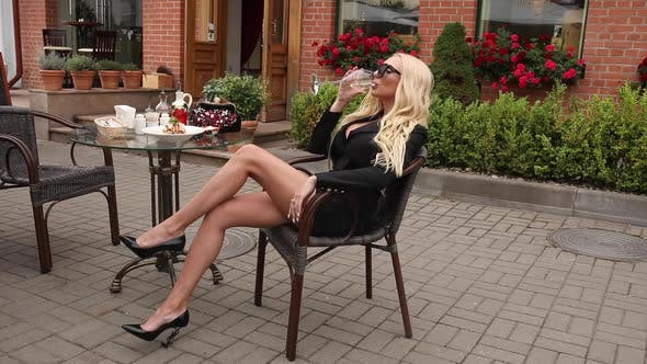 Cover Image for Adorable Fashion Blonde Female Model Enjoying Break Drinking Champagne at Outdoor Restaurant