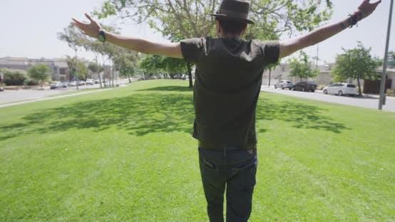 Thumbnail for Hispanic man embracing two multi ethinic friends walking through park