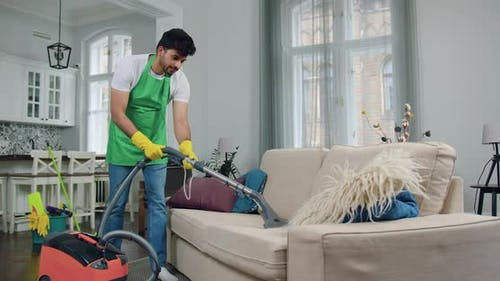 Guy in Uniform of Cleaning Service Vacuuming Comfortable Sofa During Cleaning