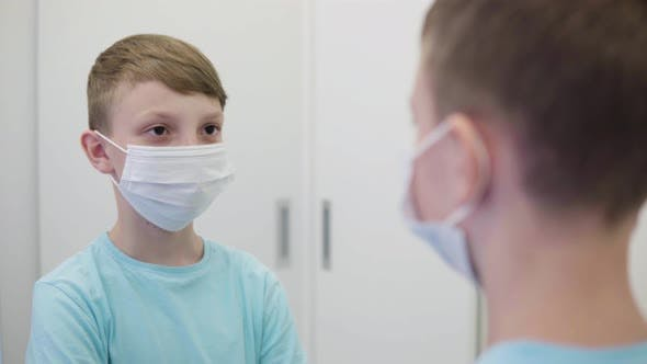 Thumbnail for A Young Boy Puts on a Face Mask in Front of a Mirror and Looks at the Camera - Closeup
