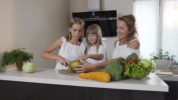 Thumbnail for Two Sisters with Their Mother in White Dresses is Cooking Healthy Vegetable Salad