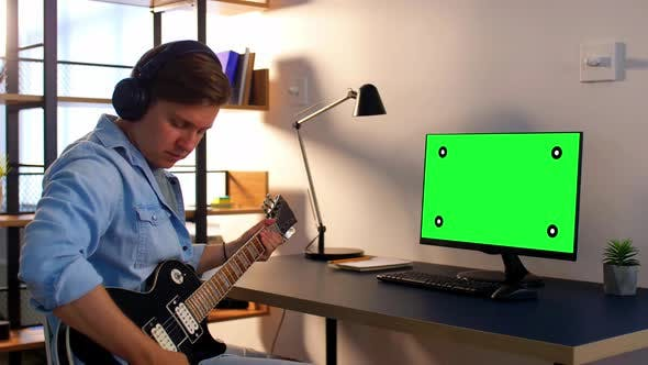 Thumbnail for Man in Headphones with Computer Playing Guitar