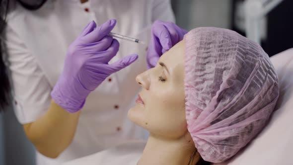 Thumbnail for Ein erfahrener Kosmetiker macht Botox im Augenbrauenbereich für eine Frau