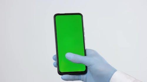 Hand in medizinischen Handschuh mit Smartphone mit grünem Bildschirm