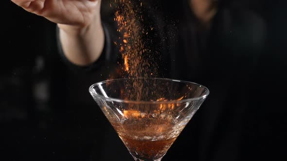 Bartender Sets Fire To Cocktail, Burning Cinnamon in Alcohol Drink on Black Background. Flames in