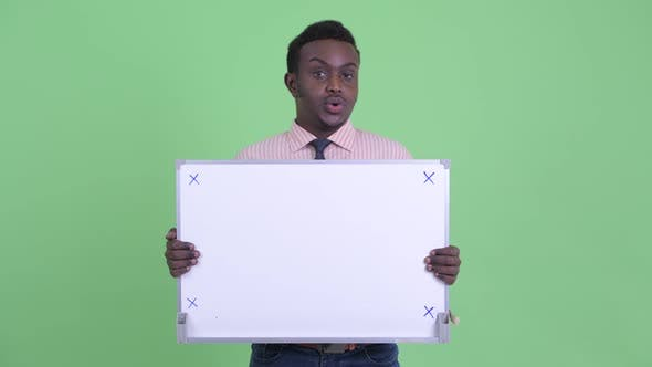 Cover Image for Stressed Young African Businessman Holding White Board