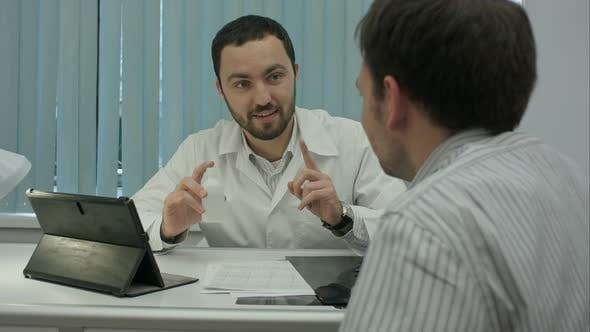 Thumbnail for Male Bearded Doctor in Clinic Advertises Preparation To Client