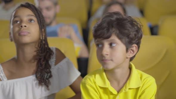 Afroamerikaner, nahöstlicher und kaukasischer Kinder sitzen im Kino und schauen Film.  Kamera
