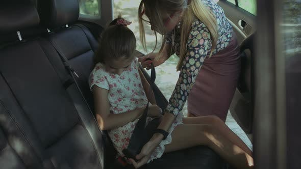 Thumbnail for Caring Mother Fastening Girl with Seat Belt in Car
