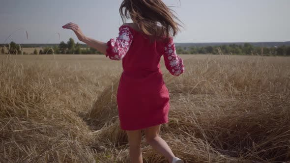 Thumbnail for Lovely Young Girl Running in Slow Motion Through a Field. Carefree Woman Enjoying Sunlight