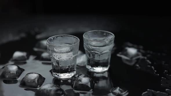 Thumbnail for Add Ice Cubes To Shot of Vodka in Glass Against Black Background. Alcohol Drink