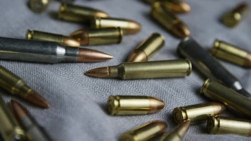 Cinematic rotating shot of bullets on a fabric surface - BULLETS 098