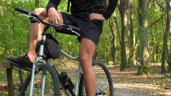 Thumbnail for A Man Sits on a Bike in a Forest - Closeup on the Lower Body
