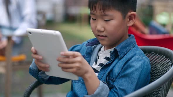 Thumbnail for Little Asian Kid Playing on Tablet in Outdoor Cafe
