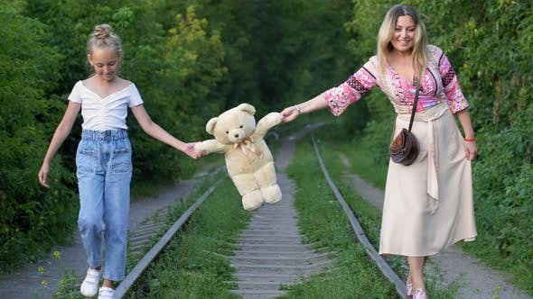 Thumbnail for Happy Mother and Daughter Carrying Teddy Bear Above Railroad