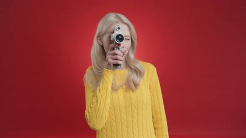 Beautiful Young Blonde Woman Shoots on Camera Making Video on Isolated Red Background