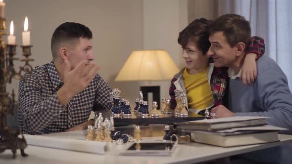Happy Caucasian Grandfather and Grandson Playing Chess Against Boy's Father. Smiling Family Spending