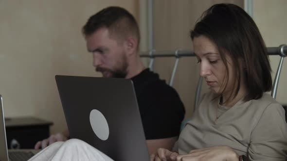 Couple On Bed Using Laptop Computers