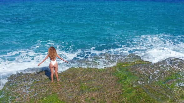 Thumbnail for Aerial View. Sexy Girl Standing on the Cliff on the Rocky Beach. A Woman Looks Into the Distance.