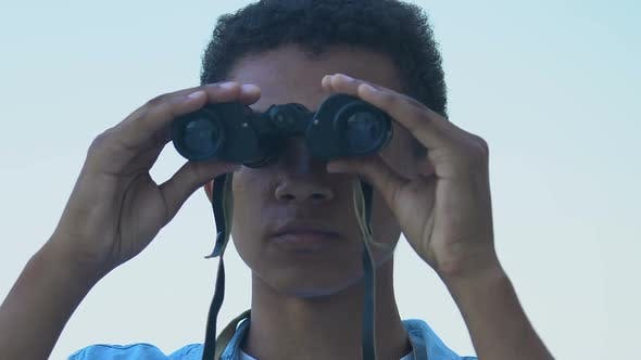 Thumbnail for Afro-American teen boy watching through binoculars
