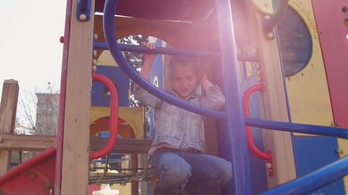 Joyful Junior Schoolgirl Poses on Attraction with Blue Tubes