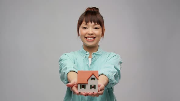 Smiling Asian Woman Holding House Model