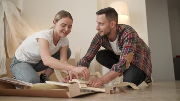 Thumbnail for Young Adults Moving in New Home, Couple Moving in Assembling Chair Furniture, Young Interracial