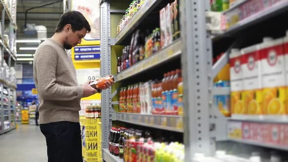 The Darkhaired Man Gravely Considering Bottles with Fruit Juices