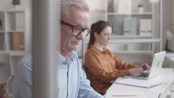 Thumbnail for Reife kaukasischen männlichen Mitarbeiter Lächeln bei der Arbeit in gemütlichem Büro