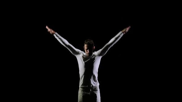 Thumbnail for Young Handsome Male Acrobat Gymnast in White Clothes on a Black Background Jumping on a Bot-up
