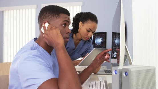 Thumbnail for Two African American doctors in blue scrubs using hospital work station