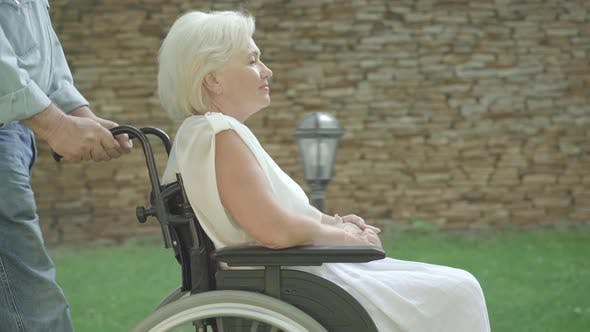 Thumbnail for Side View of Paraplegic Senior Woman Talking As Unrecognizable Man Rolling Wheelchair. Grey-haired